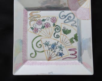 Square plate decorated with 4 japane and stylized waves hand painted porcelain. Pink and iridescent frame.