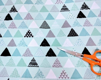 Black white and gray patterned triangle pennants on light blue,  cotton spandex (lycra) knit fabric by the yard destash