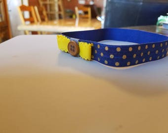 Blue and gold headband with a small yellow bow.