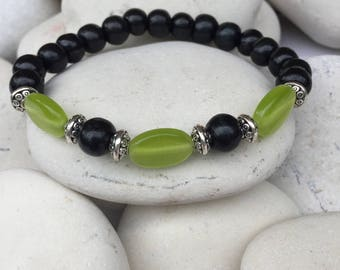 Hand made elastic bracelet, green glass beads, dark brown wood bead, with silver metallic accents