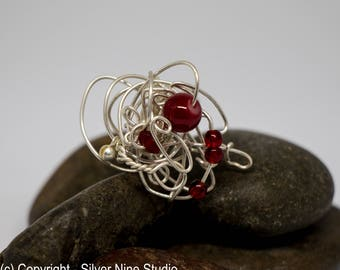 Silver wire statement ring with red bead accent