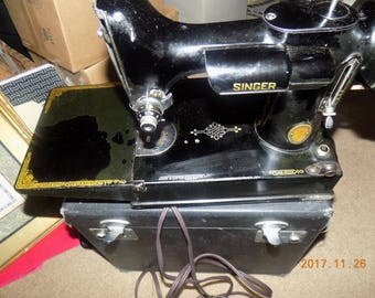 Rare singer family sewing machine in portable case with all attchments.
