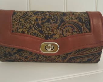 The very necessary clutch wallet with a turn lock clasp and multiple card slots and a pocket for everything.