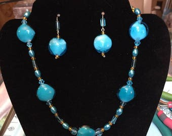 Blue glass beads with blue and orange beads for accent.