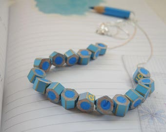 Choker necklace with small segments of the turquoise colored pencils
