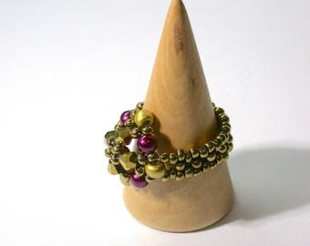 A striking ring created with gold  bicones, toho and seed beads contrasted with burgundy round beads