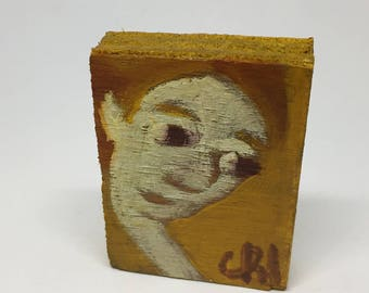 Very small painting on wood, decorative gift - face leaning on a yellow background