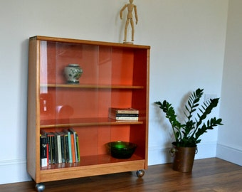 1970's Display cabinet / drinks cabinet / book case, with sliding glass doors, on metal castors.