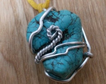 Turquoise pendant wrapped in silver colored wire
