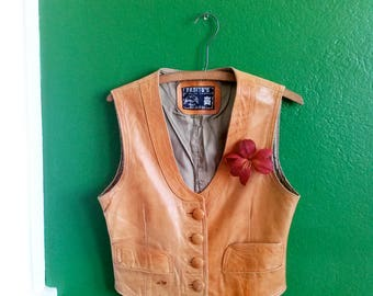 A Mexican leather vest with four buttons and a red leather lily boutonniere.