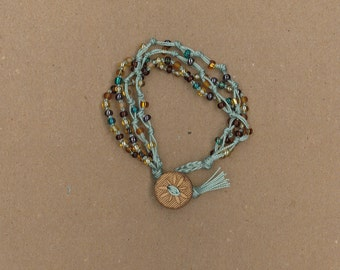 Light green knotted cord wrap bracelet with turquoise, brown, and tan seed beads