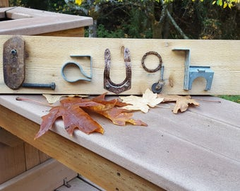 LAUGH Sign on Cedar Plank - made with re-purposed hardware.