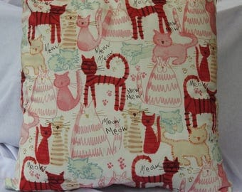 Cushion with assorted cat drawings in white, pinks etc