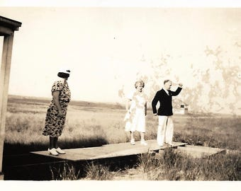 "Vintage Photo ""Do The Bossa Nova"" Formally Dressed Man Arms Waving Balancing On Board With Two Women Found Vernacular Photo"