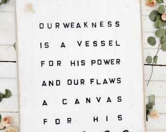 Our weakness is a vessel for his power and our flaws a canvas for his grace black and white rustic wood sign