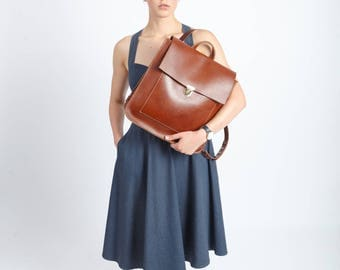 Ginger brown leather backpack with a front pocket