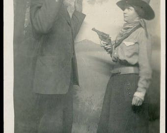 This is a Stick Up - Woman Holding a PISTOL to a Man with His ARMS In the AIR Novelty Studio Arcade Photo Postcard circa 1910