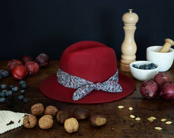 Red fedora hat decorated with a cotton scarf