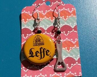 "Earrings caps of beer ""leffe honey flavor"" and a bottle opener"