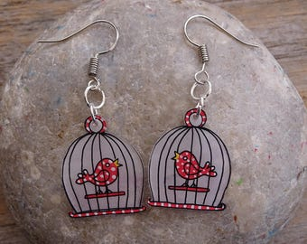 pretty red birds with polka dots in their cage