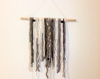yarn wall hanging • pompoms & soft gray yarn