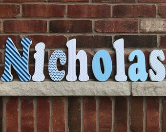 Boys wood name finished in a blue paper pattern