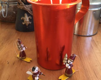 Red metal jug with soy candle