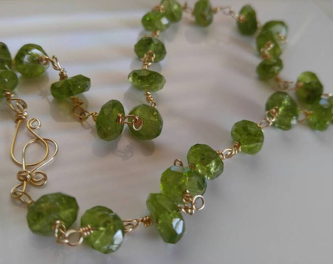 Peridot  choker necklace with 14kt gold clasp 17 inches long. Peridot wrapped in gold.