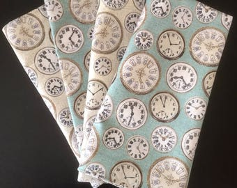 Clocks:  Blue-green napkins feature beige analog clocks in different sizes and styles.  The identical complementary side is beige.