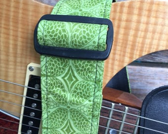 Guitar strap with green on green print.