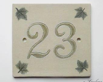 Door number 23 in sandstone, green on ecru background, decorative leaves Ivy