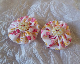 set of two clips made with yoyo flowers in shades of pink and yellow