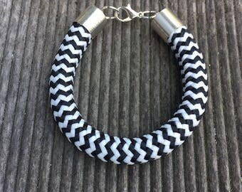 Silver caps and large black and white cord bracelet