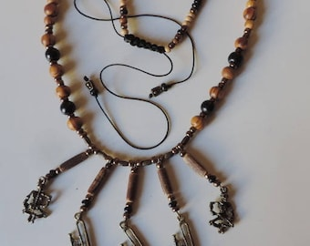 Composition Danse macabre: skeletons and bronze saxophone necklace on wood