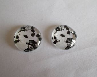 1 set of 2 glass cabochons flunks out black leaves on white background