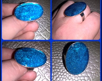 Adjustable size ring with oval shaped translucent resin dyed blue