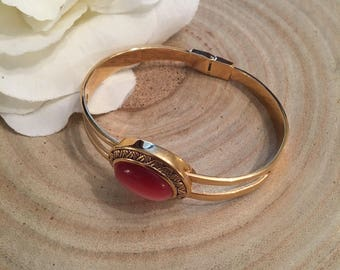 Vintage hinged gold tone bracelet with reddish pink stone