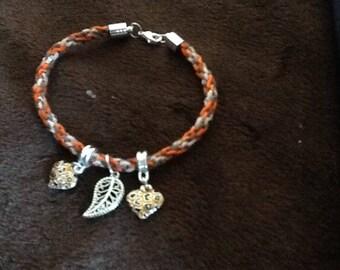 A kumihimo bracelet with a leaf charm
