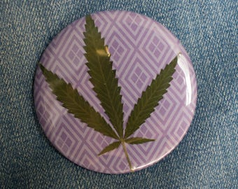 Pressed Cannabis Leaf Button on Purple Background
