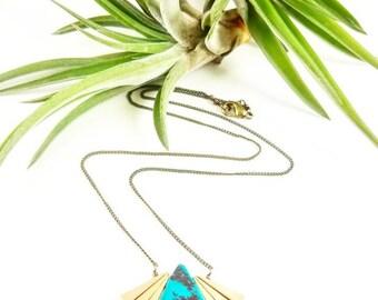 Turquoise stone teardrop with tiny raw brass triangles.