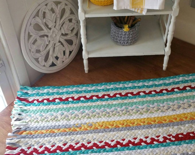 Turquoise,  red, yellow braided rug