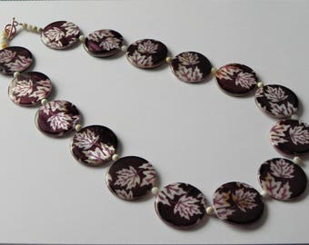 Printed burgundy shell with leaf design and white opal necklace.