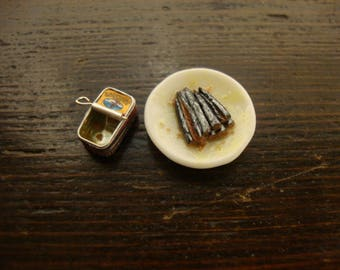 miniature can of  sardines  empty + dish with sardines