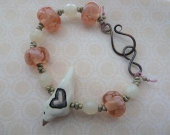 handmade pink ceramic bird and lampwork copper bracelet, UK jewellery