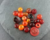 20 assorted orange and red glass spacer beads.