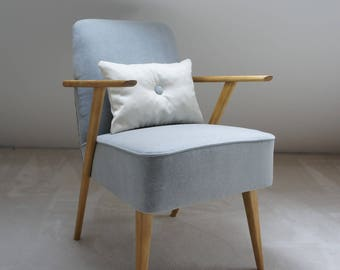 Light gray vintage armchair with armrests