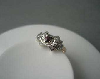 Antique ornate 14 karat solid gold ring decorated with a natural garnet and zircons.