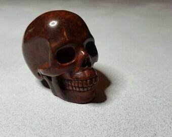 "2"" Red jasper carved human skull."