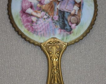 Vintage boudoir hand mirror with courting scene