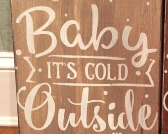 "Hand-painted, wood sign, ""Baby it's cold outside."""